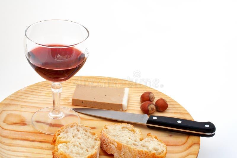 Le pâté, le pain, la glace de vin rouge, les noisettes et le couteau sur le bois plat photo stock