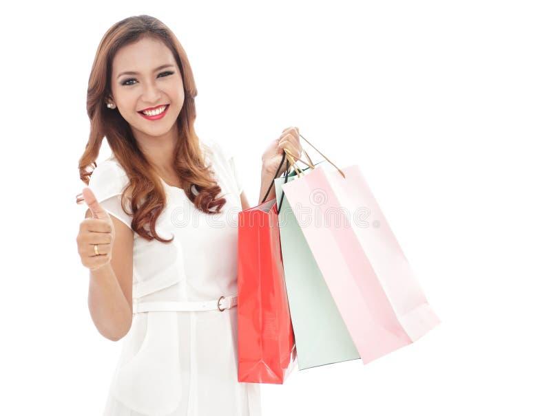 le påsar för shopping för skönhetkvinna hållande medan tummar upp royaltyfria bilder