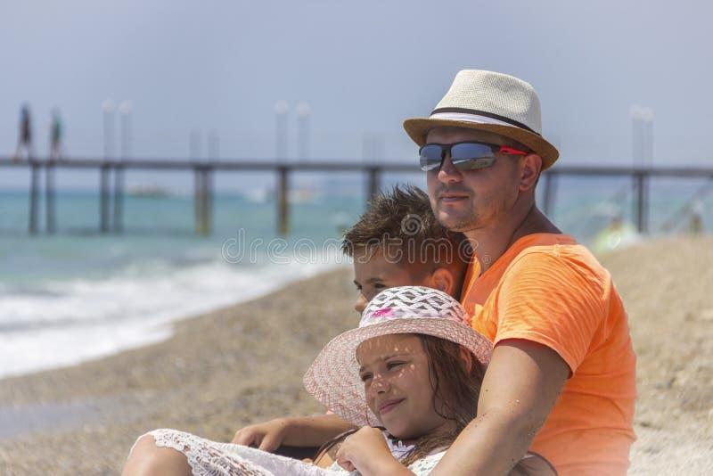 Le père affectueux avec son fils et la fille dans l'obhimku se reposent sur le bord de la mer ou l'océan photo stock