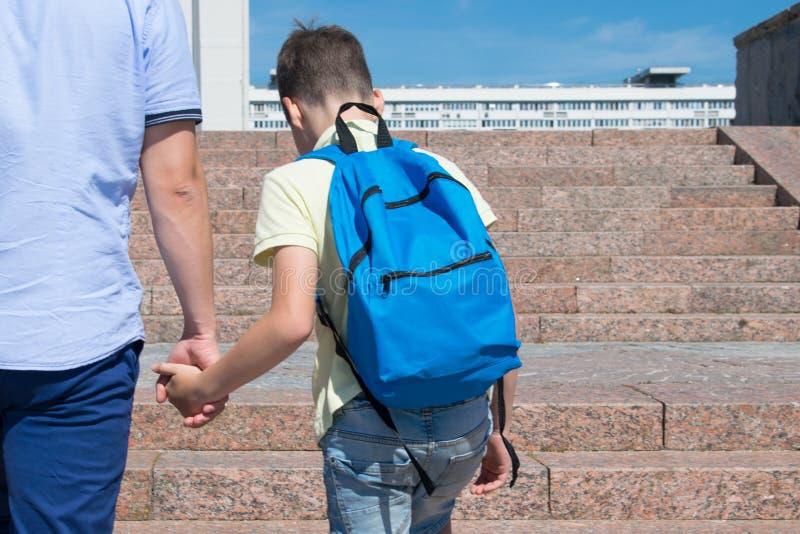 Le père aide à monter l'échelle de la connaissance, vers le haut de image libre de droits