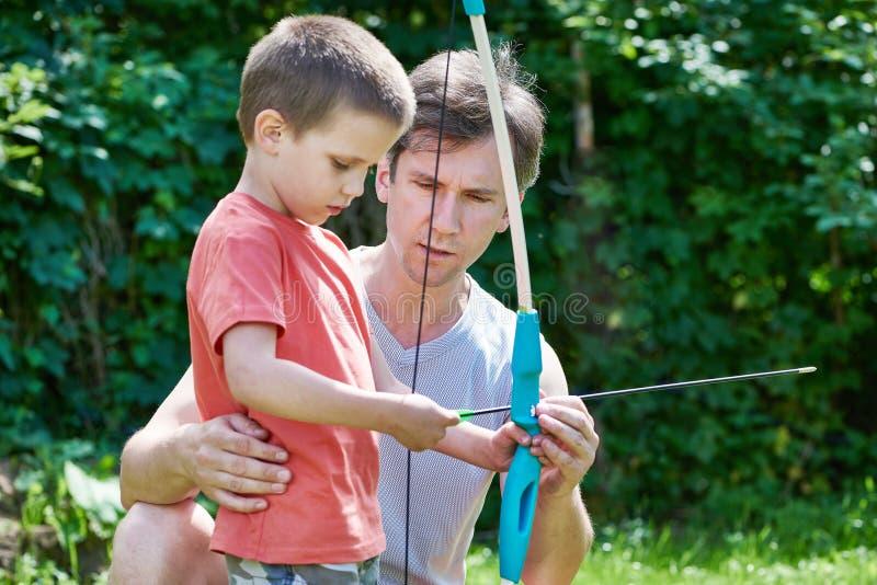 Le père apprend son fils pour tirer de l'arc photos libres de droits