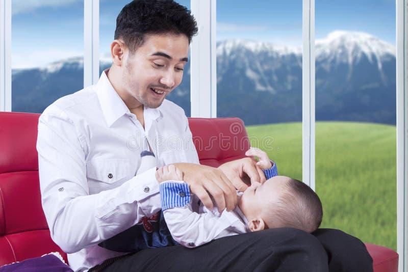 Le père attirant remplacent son usage de bébé photographie stock