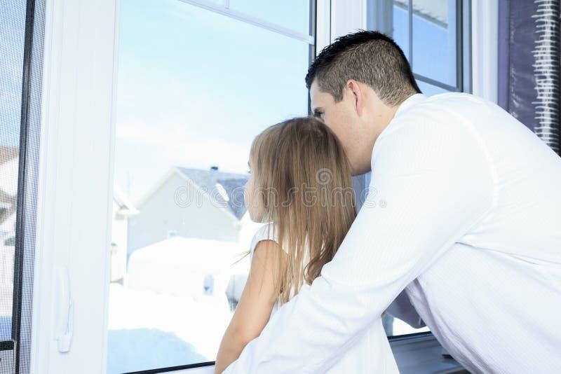 Le père avec est fille près d'une fenêtre photo libre de droits
