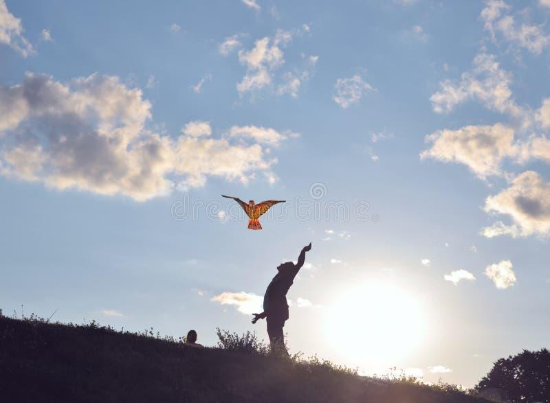Le père avec la fille pilote le cerf-volant de jouet image stock