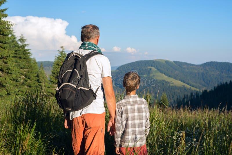 Le père avec le fils se tiennent sur un pré alpin parmi un gra luxuriant photos stock