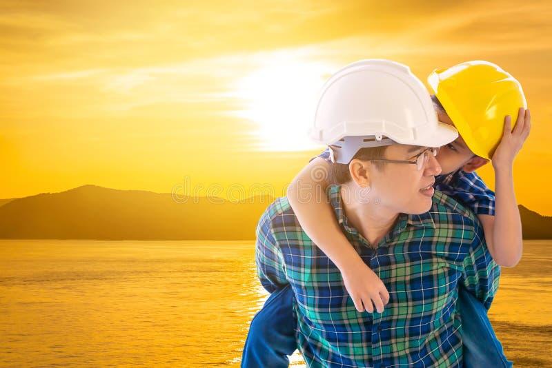 Le père bâtisseur transportant son fils dans le ciel doré nuage la mer de l'île et la famille bosse le concept futur image libre de droits