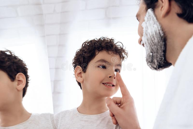 Le père barbu abîme le nez du fils avec raser la mousse photos libres de droits