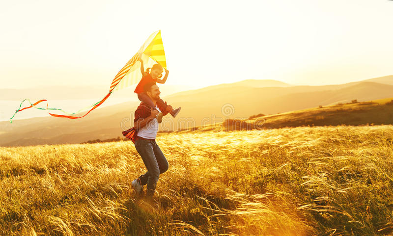 Le père de famille et la fille heureux d'enfant courent avec le cerf-volant sur le pré image libre de droits