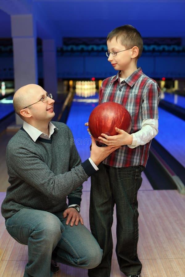 Le père donne la bille de fils pour le bowling images stock