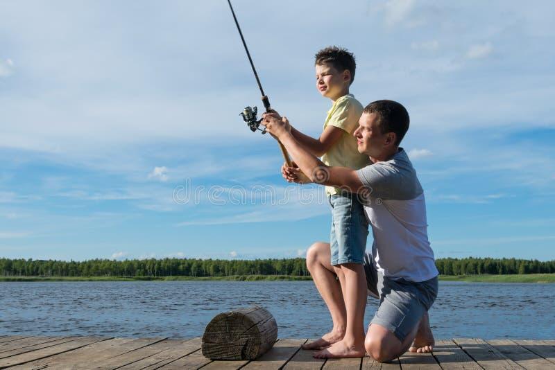 Le père enseigne le fils à pêcher sur tourner sur le lac un jour de congé de famille photo libre de droits
