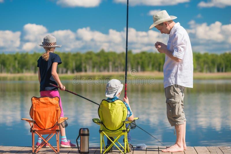 Le père enseigne ses enfants à pêcher sur un poteau de pêche au tarte images stock