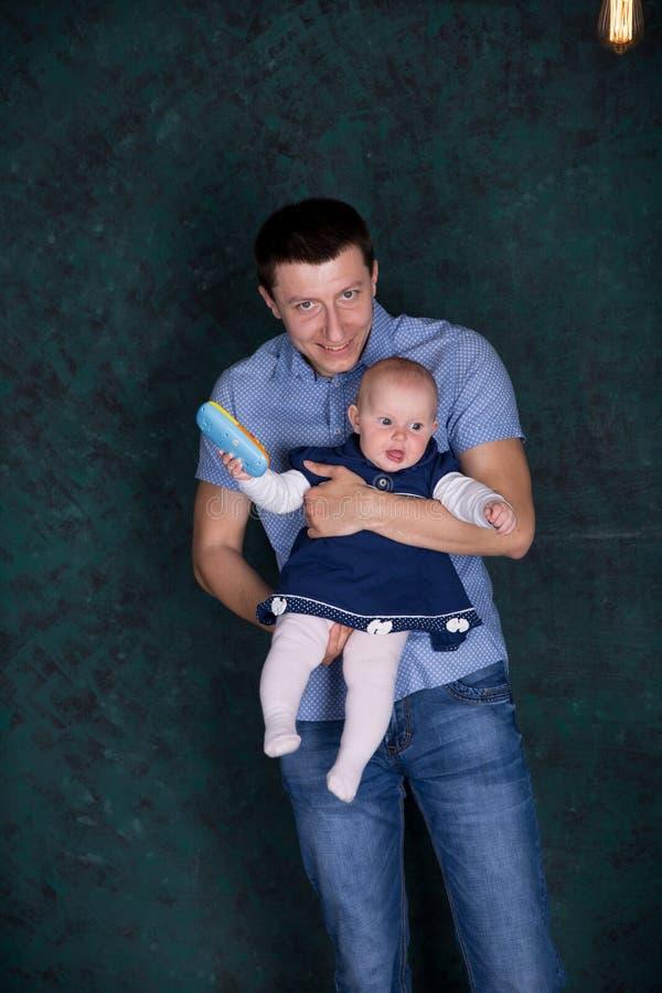 Le père est tenant et étreignant sa fille de bébé photo stock