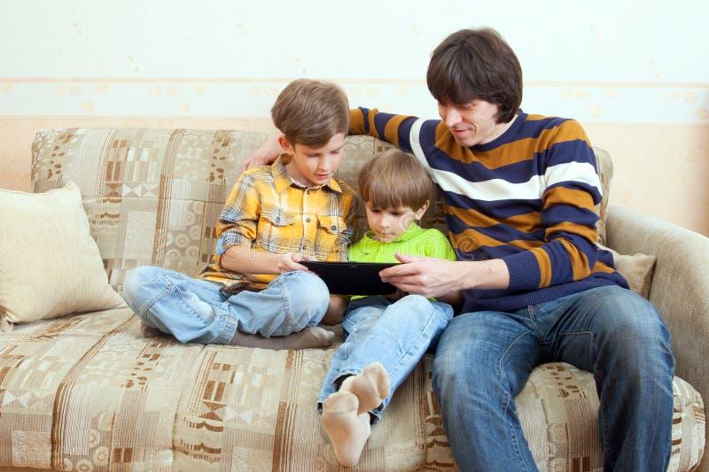 Le père et deux garçons jouent sur la tablette image stock