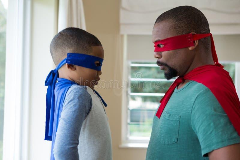 Le père et le fils dans le super héros costument sembler face à face photo libre de droits