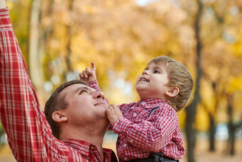 Le père et le fils jouent et ont l'amusement en parc de ville d'automne Ils posant, sourire, jouant Arbres jaunes lumineux images libres de droits