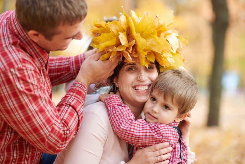 Le père et le fils ont mis les feuilles tombées jaunes sur la tête de mère La famille heureuse est en parc de ville d'automne Enf image libre de droits