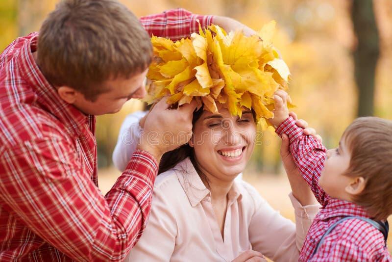 Le père et le fils ont mis les feuilles tombées jaunes sur la tête de mère La famille heureuse est en parc de ville d'automne Enf photos libres de droits