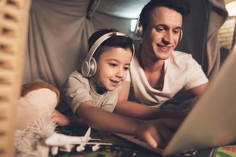 Le père et le fils parlent sur le skype à la famille sur l'ordinateur portable la nuit à la maison photos stock