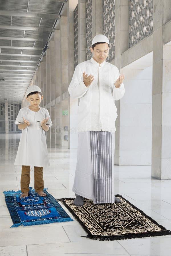 Le père et l'enfant prie à un DIEU dans la mosquée images libres de droits