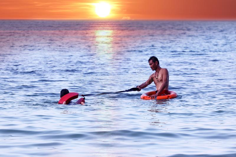 Le père et la fille asiatiques sont enseignants et formants la garde ou la délivrance de vie sur la plage photo stock