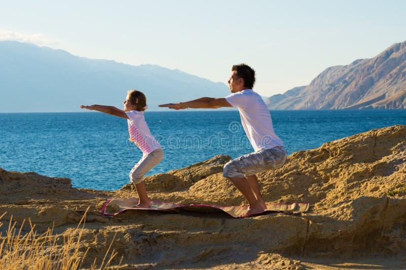 Le père et la fille faisant le yoga s'exercent sur la plage image libre de droits