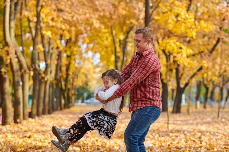 Le père et la fille jouent et ont l'amusement en parc de ville d'automne Ils posant, sourire, jouant Arbres jaunes lumineux photographie stock libre de droits