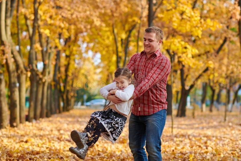 Le père et la fille jouent et ont l'amusement en parc de ville d'automne Ils posant, sourire, jouant Arbres jaunes lumineux images stock