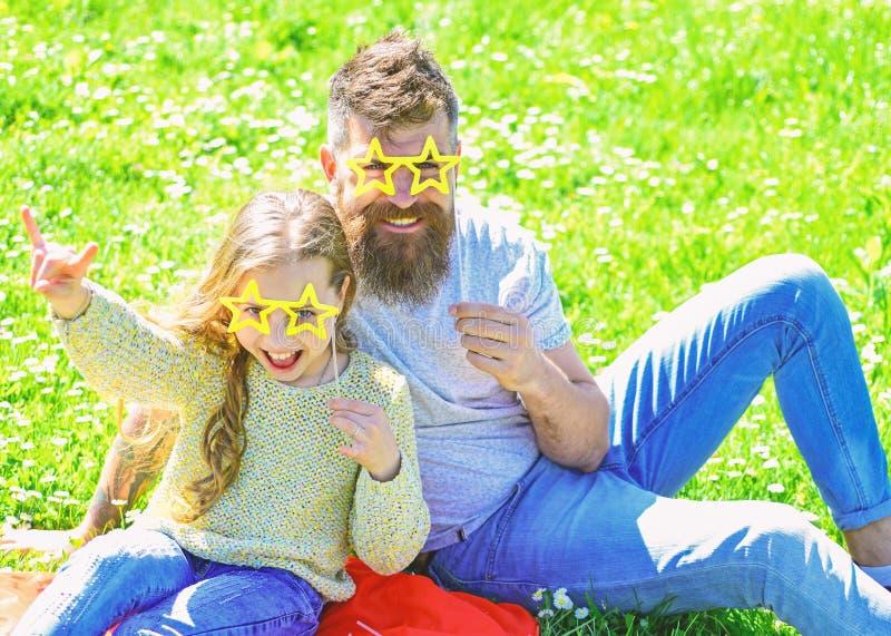Le père et la fille s'assied sur l'herbe au grassplot, fond vert Concept de superstar Enfant et papa posant avec l'étoile photo libre de droits