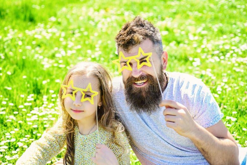 Le père et la fille s'assied sur l'herbe au grassplot, fond vert Concept de superstar La famille dépensent des loisirs dehors photos libres de droits