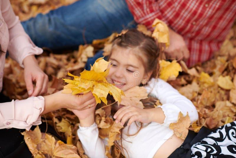 Le père et la fille se trouvent sur les feuilles jaunes et ont l'amusement en parc de ville d'automne Ils posant, sourire, jouant photos libres de droits