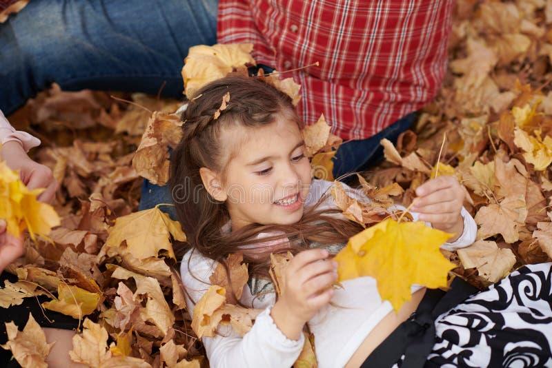 Le père et la fille se trouvent sur les feuilles jaunes et ont l'amusement en parc de ville d'automne Ils posant, sourire, jouant image libre de droits