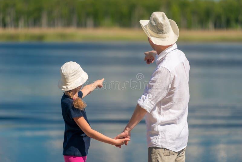 Le père et la fille sur le pilier près de l'étang montrent l'eau avec a images stock