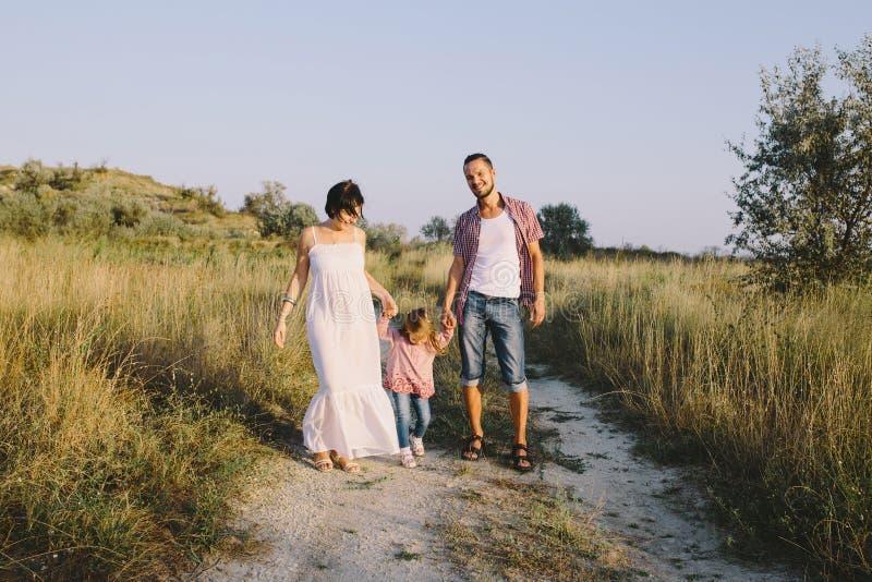 Le père et la mère enceinte mène sa fille par la main extérieure image stock