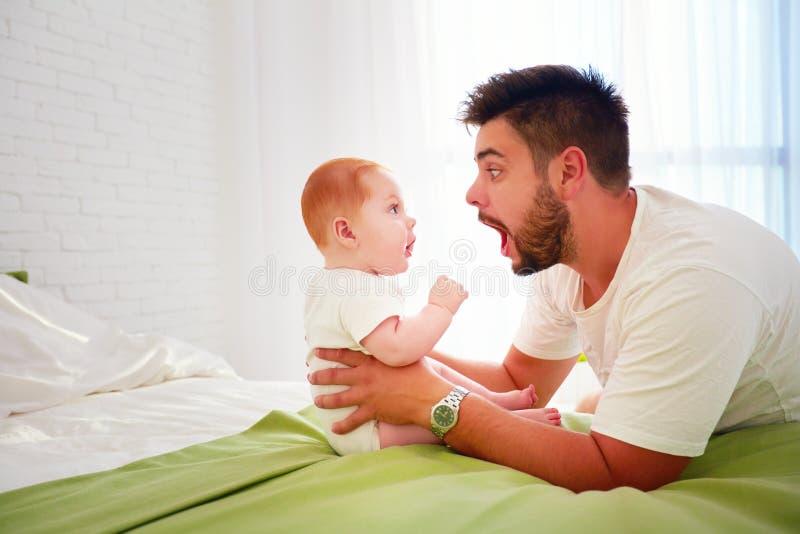Le père et le bébé drôles regardent l'un l'autre avec la stupéfaction photos stock