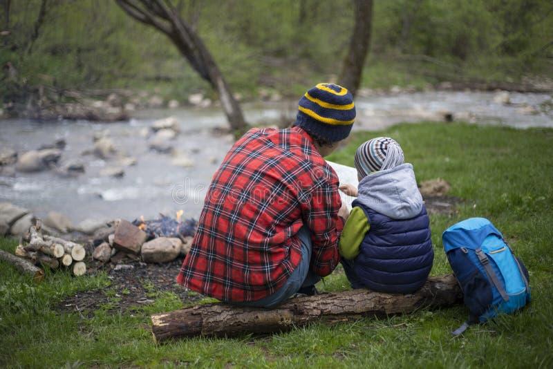Le père et le fils s'asseyant près d'un feu de camp au terrain de camping et sont l photo libre de droits