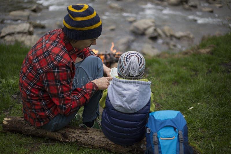 Le père et le fils s'asseyant près d'un feu de camp au terrain de camping et sont l images stock