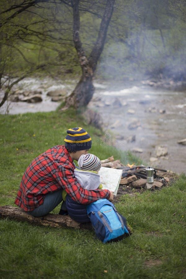 Le père et le fils s'asseyant près d'un feu de camp au terrain de camping et sont l image stock