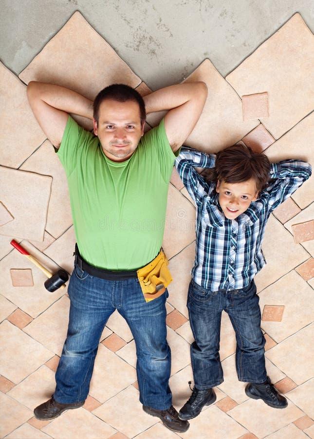 Le père et le fils se reposant sur les carrelages non finis apprêtent photo libre de droits