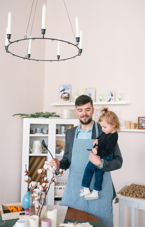 Le père et sa fille de bébé préparent la nourriture dans la cuisine image stock