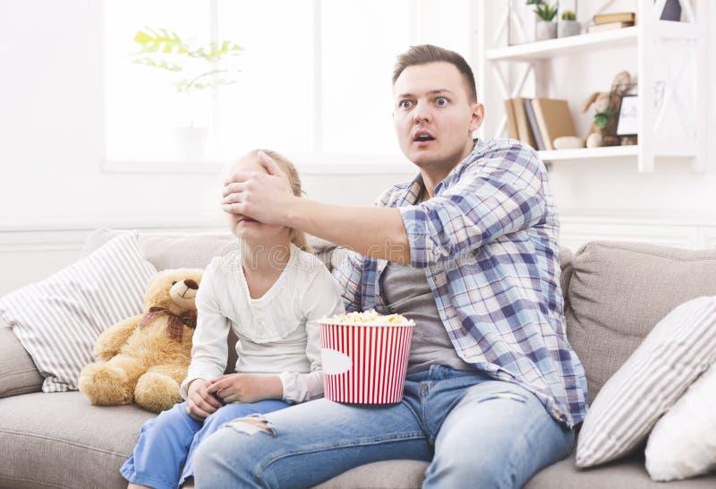 Le père ferme ses yeux de fille tout en observant le film photo stock