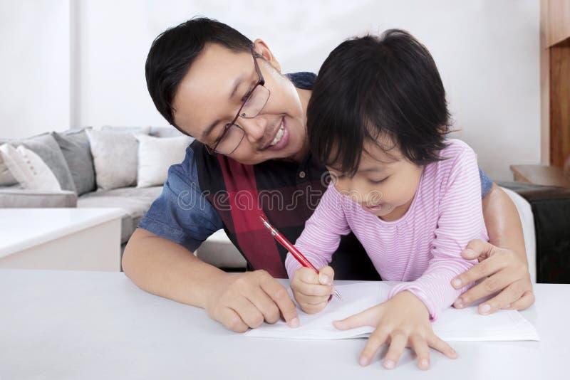 Le père guide sa fille faisant le travail photographie stock