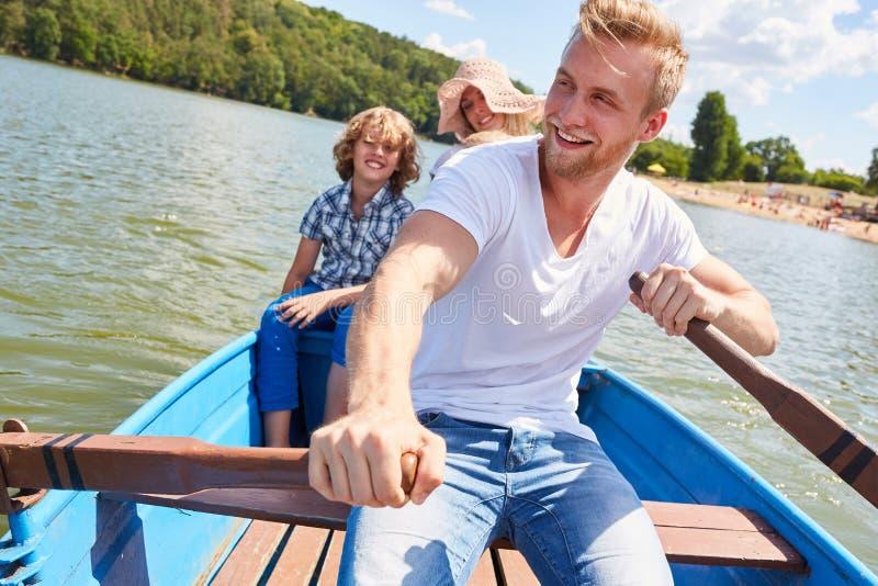 Le père heureux rame sa famille dans le bateau photographie stock libre de droits