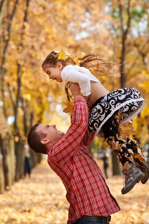 Le père jette la fille haute en parc de ville d'automne Ils posant, sourire, jouant Arbres jaunes lumineux images stock