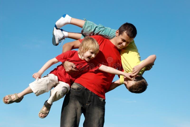Le père jouant avec des fils contre le ciel photos stock