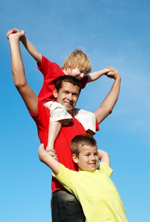 Le père jouant avec des fils contre le ciel image stock