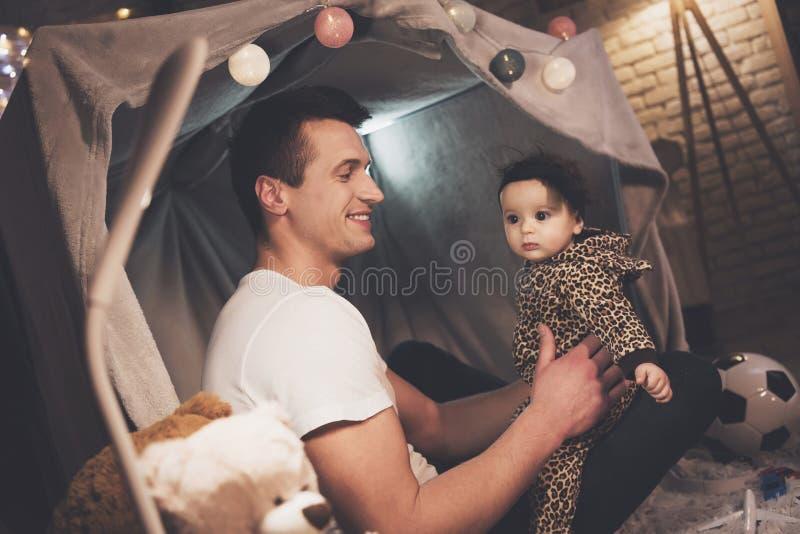 Le père joue avec la petite fille de bébé la nuit à la maison image libre de droits