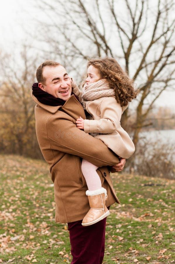 Le père joue avec sa petite fille bouclée la tenant dans des ses bras photos stock