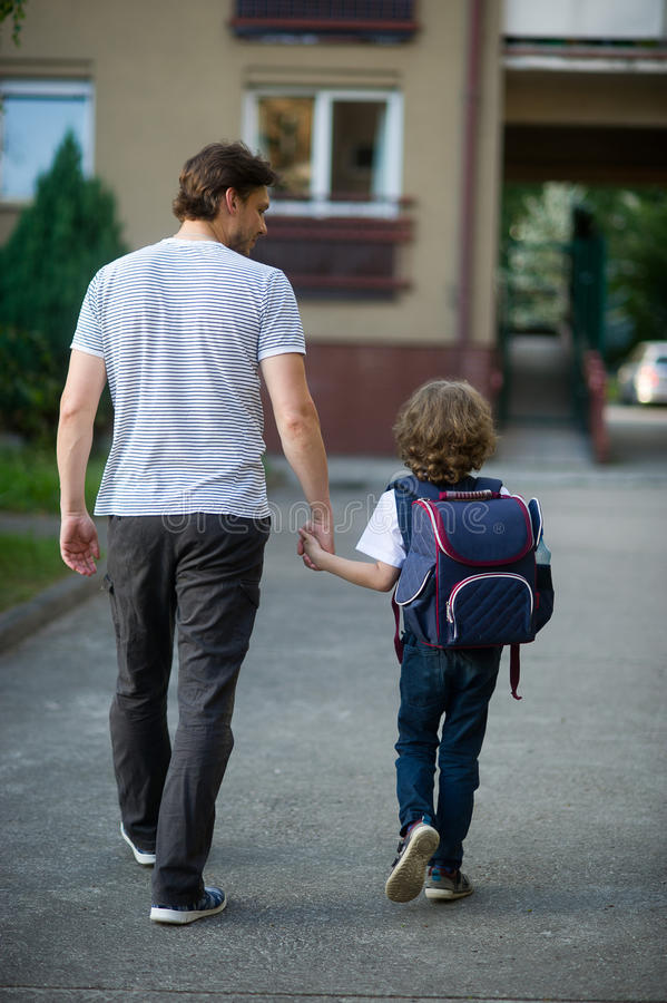 Le père mène par la main son fils à l'école image libre de droits