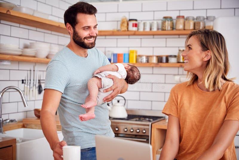 Le père multitâche Holds Baby Son et fait la boisson chaude pendant que la mère utilise l'ordinateur portable et mange le petit d image stock