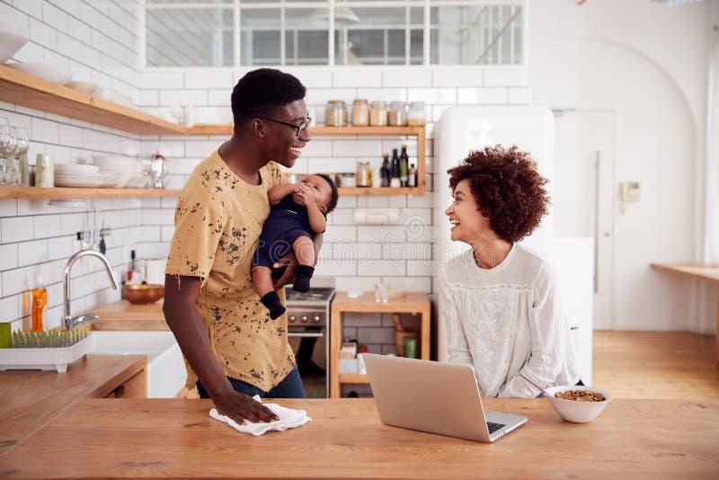 Le père multitâche Holds Baby Son et nettoie la surface pendant que la mère utilise l'ordinateur portable et mange le petit déjeu image libre de droits